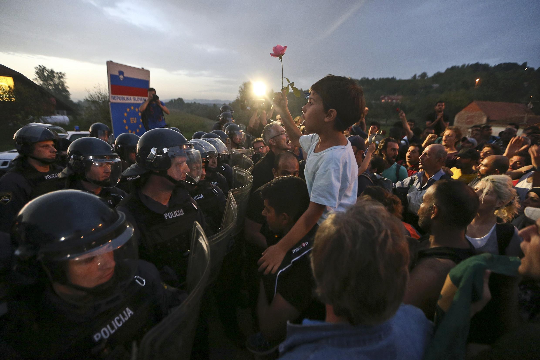 Em Harmica, refugiados pedem que a polícia eslovena libere passagem apra seguirem viagem rumo ao norte da Europa.