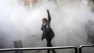 Une Iranienne lève le poing au milieu de gaz lacrymogènes devant l'université de Téhéran lors d'une manifestation contre le pouvoir le 30 décembre 2017