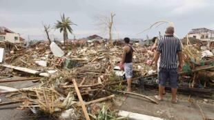 Sobrevivientes ante la destrucción total de un sector de Tacloban, en el centro de Filipinas, el 9 de noviembre de 2013.