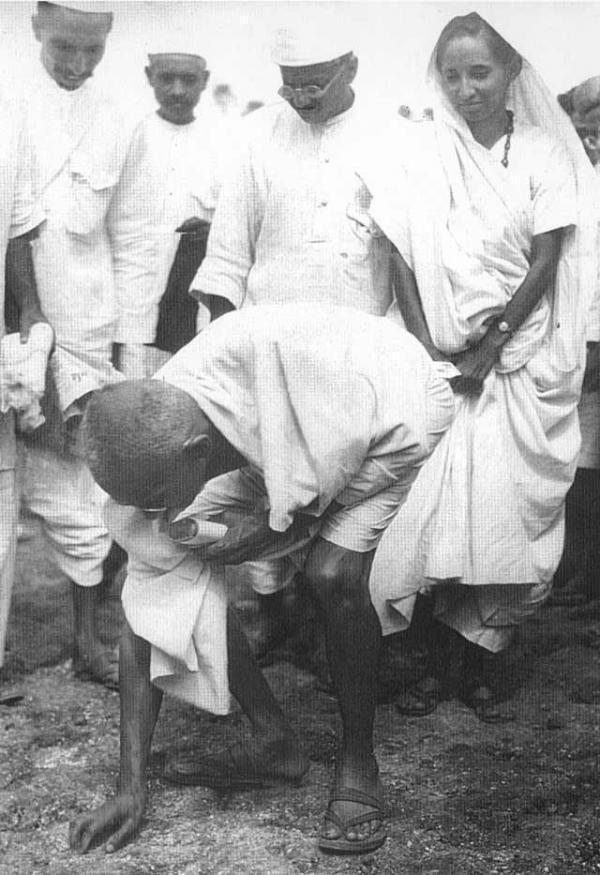 Gandhi à Dandi, le 5 avril 1930, ramassant une poignée de boue salée.