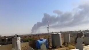 伊拉克北部的巴基炼油厂上空冒着浓烟,2014年6月18日。