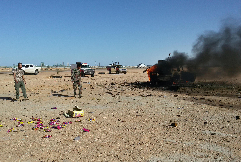 Un véhicule en feu après des affrontements entre l'armée libyenne et des combattants des Brigades de défense de Benghazi, à Ras Lanuf le 14 mars 2017.