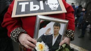 Une femme porte une pancarte représentant Poutine et une photo de Nemtsov, lors de la marche du 1er mars 2015 à Moscou.