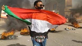Un manifestant soudanais brandit le drapeau national lors d'un défilé contre la retraite forcée de plusieurs militaires, à Khartoum, le 20 février 2020.