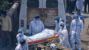 Familiares y trabajadores con equipos de protección llevan los cuerpos de las víctimas de Covid-19 a un crematorio de Nueva Delhi, en India, el 27 de abril de 2021