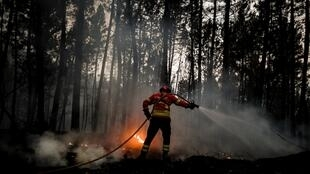 Bombeiro tenta extinguir um incêndio em Vale da Cuba, perto da aldeia de Isna, na região portuguesa de Castelo Branco.