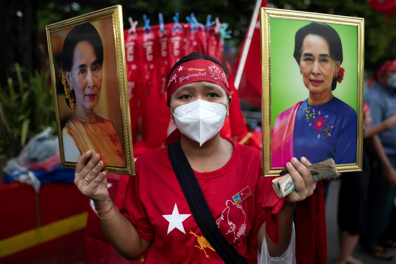 (法广存档图片)Image d'archive RFI : Un partisan de la Ligue nationale pour la démocratie (NLD) tient deux portraits d'Aung San Suu Kyi à Yangon, au Myanmar, le 9 novembre 2020.