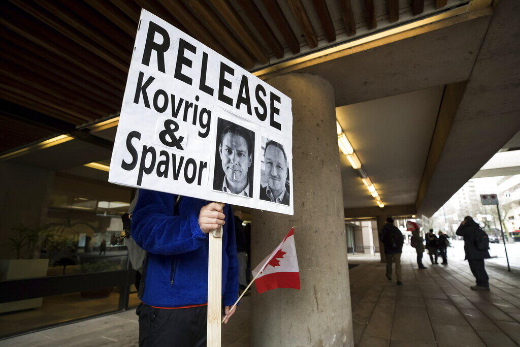 A young man holds a sign bearing photographs of Michael Kovrig and Michael Spavor, who have been detained in China for more than a year, outside British Columbia Supreme Court where Huawei chief financial officer Meng Wanzhou was attending a hearing, in Vancouver, on Tuesday January 21, 2020. (Darryl Dyck/The Canadian Press via AP)