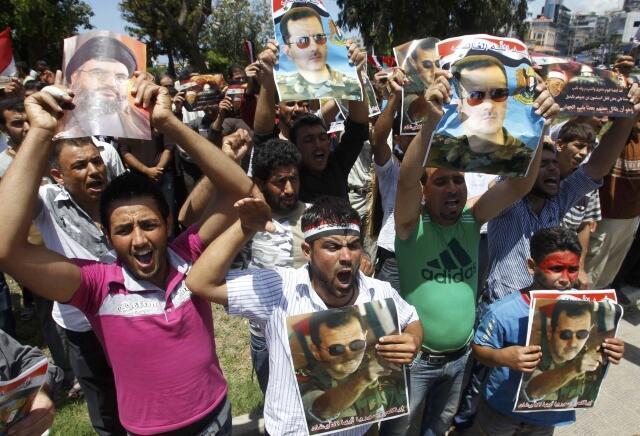 Sírios carregam cartazes com fotos de Assad e Nasrallah (à esquerda), em manifestação de apoio ao regime sírio, em Sidon, no sul do Líbano.