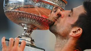 Le Serbe Novak Djokovic embrasse son trophée après sa victoire en finale contre le Grec Stefanos Tsitsipas, à Roland-Garros, le 13 juin 2021