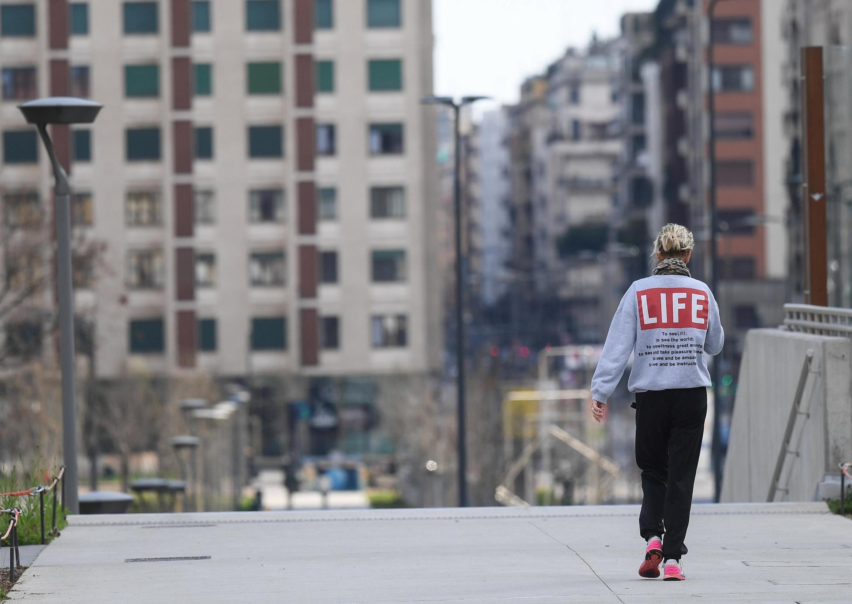 En Italie, une femme marche dans une rue déserte à Milan, le 15 mars 2020.