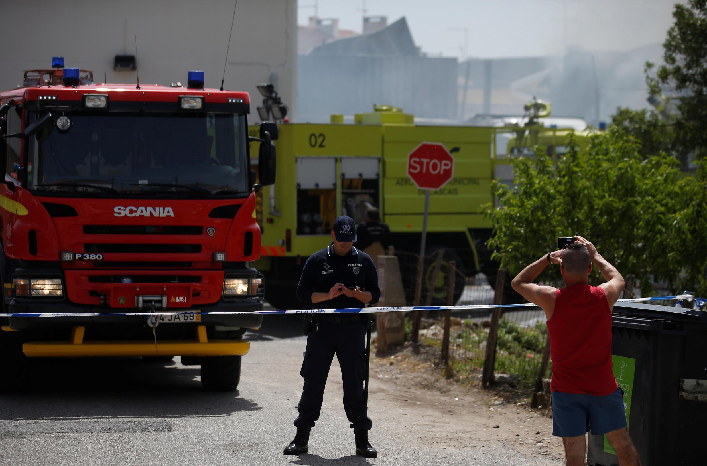 Homem fotografa região do acidente, perto de Lisboa, que foi isolada pelos bombeiros