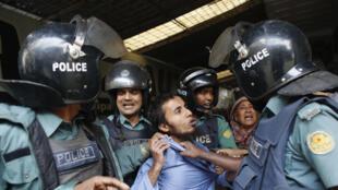 Полиция задерживает манифестанта в Дакке 27 декабря 2013.