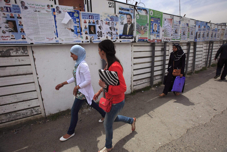 Des femmes passent le long de panneaux d'affichage pour les élections législatives, à Alger, le 9 mai 2012.