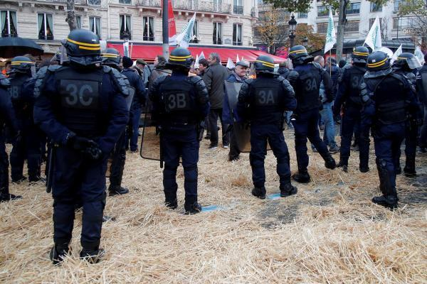 French farmers face off with French CRS police after spreading hay outside Fouquet's restaurant on the Champs Elysees avenue in Paris as part of a protest against low incomes and growing criticism of agricultural policy, 27 November 2019.