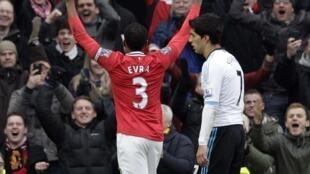 Dan wasan Manchester United Patirce Evra lokacin da yake murnar lashe wasa kusa da suarez na liverpool a filin wasa na Old Trafford inda Manchester ta doke Liverpool ci 2-1