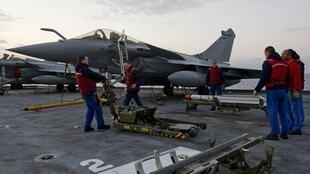 A missile is loaded under the wing of a Rafale fighter jet aboard the Charles de Gaulle aircraft carrier, 23 March 2011