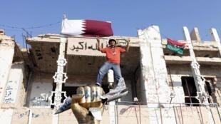 Rebelde na Líbia comemora vitória em Trípoli, em frente à residência de Kadafi.