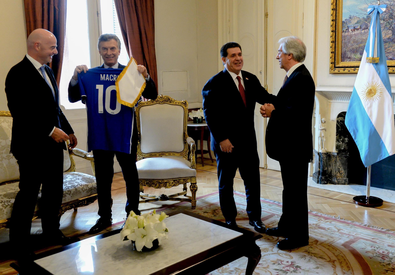 El presidente de Argentina, Mauricio Macri, sostiene una camiseta de fútbol, mientras el presidente de la FIFA, Gianni Infantino (izquierda) rie, y el presidente de Paraguay, Horacio Cartes, y el de Uruguay, Tabaré Vázquez conversan durante la conferencia