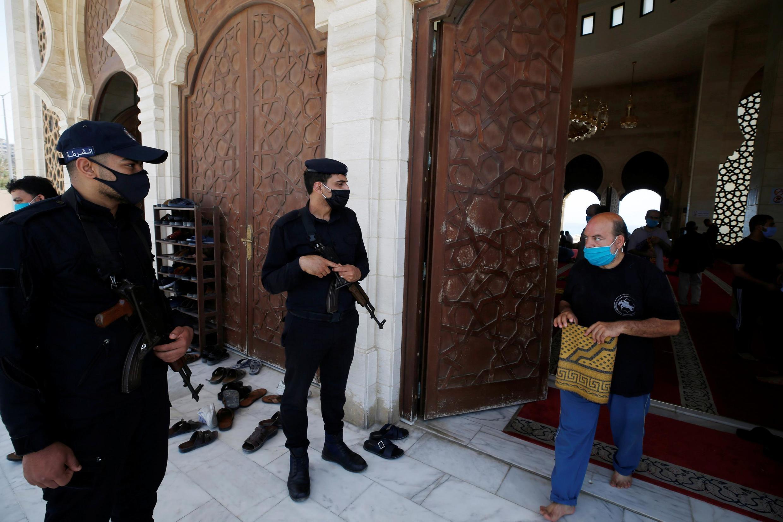 Des policiers montent la garde devant une mosquée, le vendredi 22 mai 2020, dans le nord de la bande de Gaza, alors que l'on craint une flambée de l'épidémie dans cette enclave sous blocus israélien.