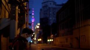 31日晚,大上海,一名戴着口罩的男子在差不多空蕩蕩的大街走路。