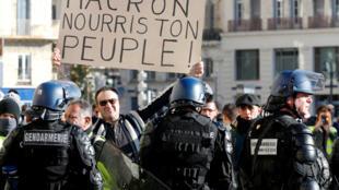 """França ansiosa por discurso de Macron para tentar superar crise dos """"coletes amarelos"""". Foto: protesto em Marseille neste domingo(8/12). Cartaz: """"Macron, alimente seu povo!""""."""