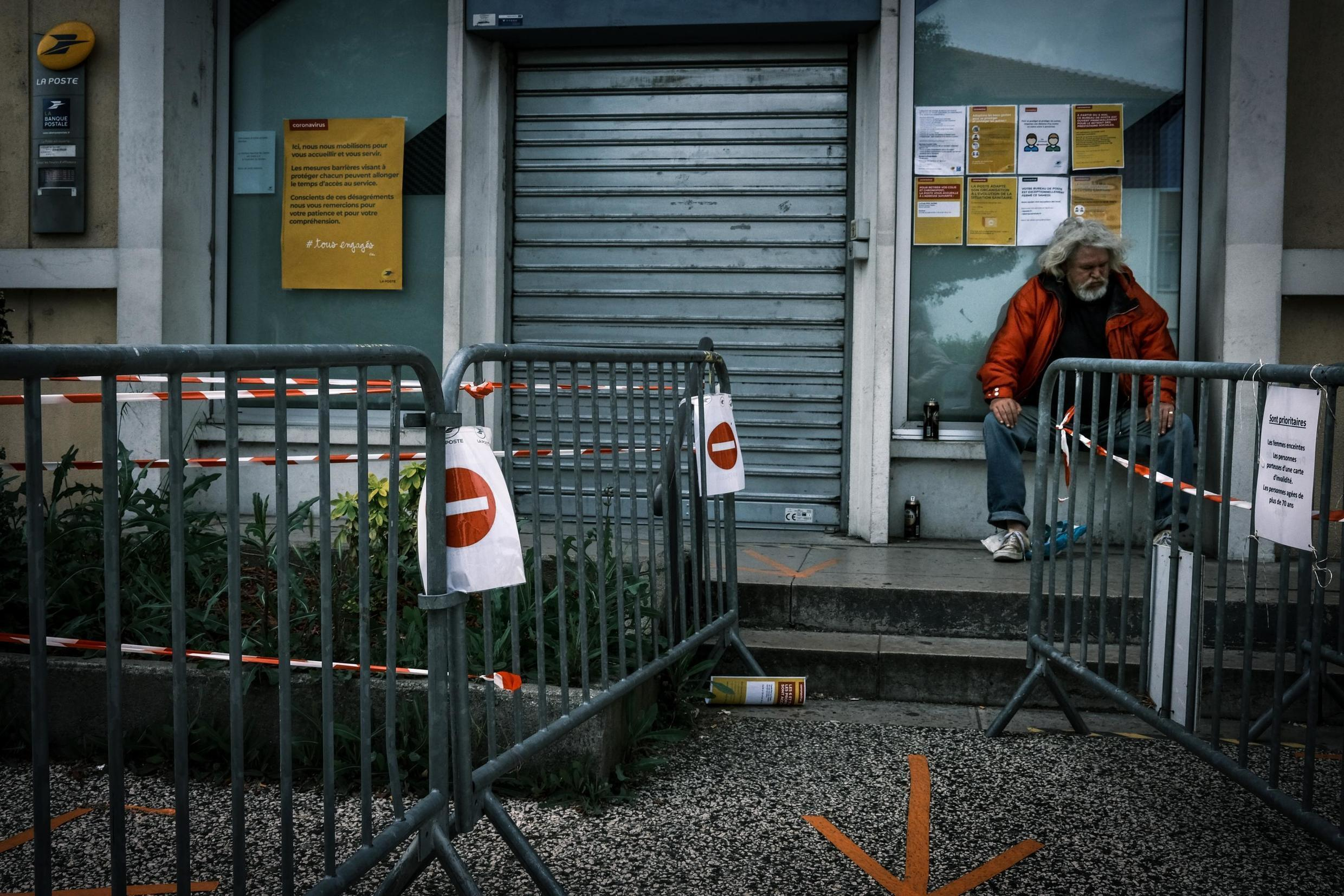 A homeless man outside the post office in Givors, near Lyon, France, 9 May 2020.