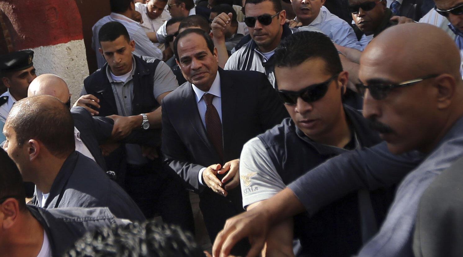 Favorito nas eleições presidenciais egípcias, Abdel Fattah al-Sissi, ao centro, chega com seguranças para votar no Cairo.