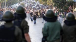 Les officiers de sécurité palestiniens devant les protestants lors d'une manifestation à Hébron contre la chèreté de la vie, le 10 septembre 2012.