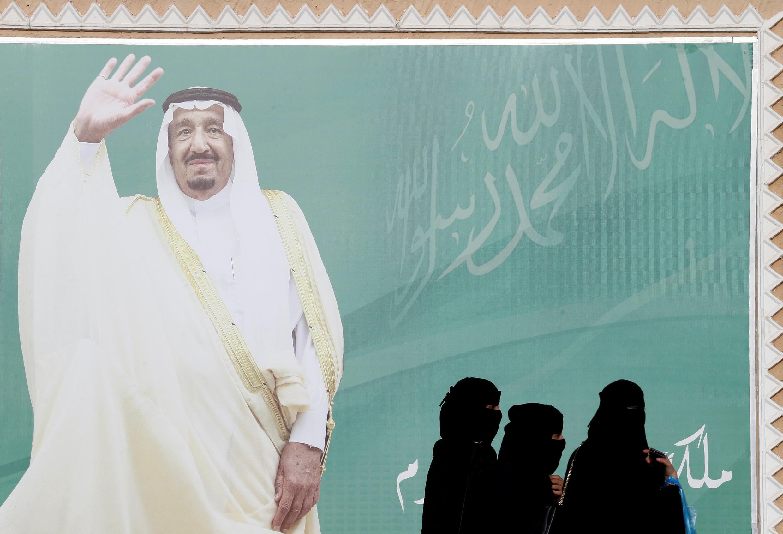 Mulheres caminham junto a um cartaz do rei Salman bin Abdulaziz Al Saud da Arábia Saudita em Riade.
