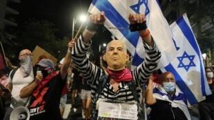 Un manifestant porte un masque représentant Benyamin Netanyahu menotté lors d'un rassemblement près de la résidence du Premier ministre à Jérusalem, le 29 août 2020.