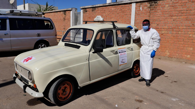 Au volant de sa 4L, paré d'une tenue de protection, Hervé, chauffeur de taxi de 29 ans. Il est volontaire pour SOS Taxi à Antananarivo à Madagascar.