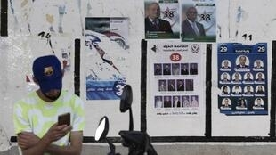 Un Algérien regarde son téléphone devant des affiches électorales pour les législatives du 12 juin 2021 à Alger.