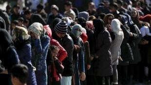 Des migrants attendent la distribution de nourriture dans un camp de Schisto, près d'Athènes, le 25 février 2016.