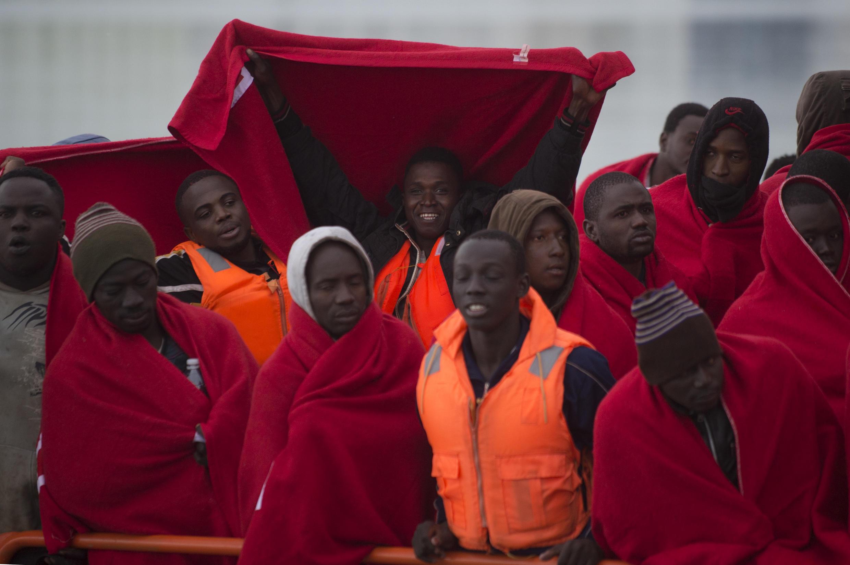 Un groupe de migrants s'embarque dans des couvertures de la Croix-Rouge à bord d'un navire de la garde côtière espagnole alors qu'il arrive au port de Malaga, dans le sud de l'Espagne, le 13 janvier 2018.
