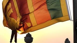 An air force officer holds Sri Lanka's national flag in Colombo to celebrate the country's 65th Independence day