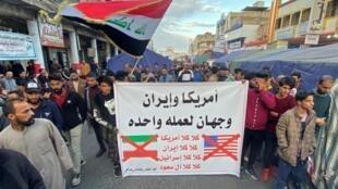 Sur la pancarte on peut lire «L'Amérique et l'Iran deux faces de la même pièce, non non Amérique, non non Iran, non non Israël, non non Saoudiens» lors des manifestations à travers le pays (ici, à Nassiriya), ce vendredi 10 janvier 2020.