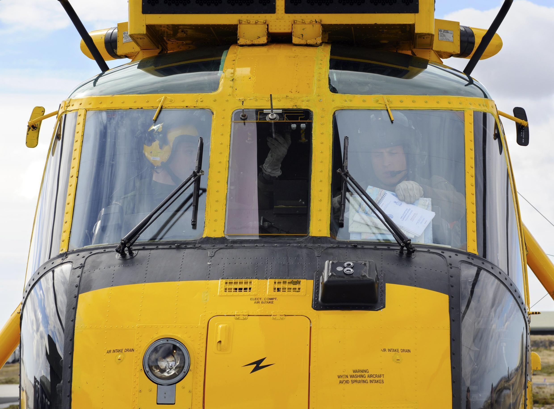 O príncipe William (à dir.) se preparar para uma saída com a tripulação nas Ilhas Malvinas.