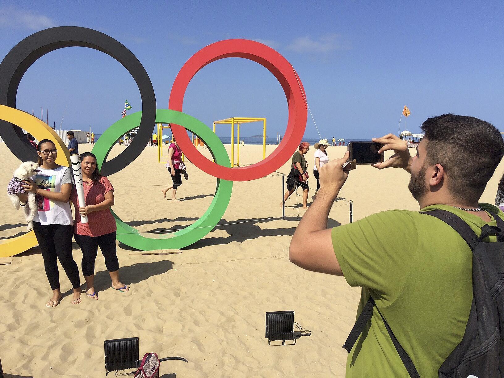 Des touristes posent devant les anneaux olympiques sur la plage de Copacabana à  Rio de Janeiro.
