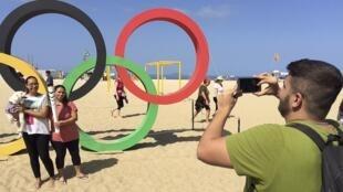 Turistas posan al lado de una réplica de la torcha olímpica en la playa de Copacabana.