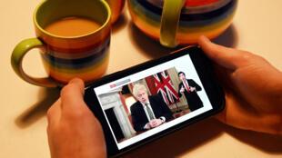 Una persona mira en su teléfono móvil un video del primer ministro británico Boris Johnson anunciando un nuevo confinamiento, el 4 de enero de 2020 en Londres