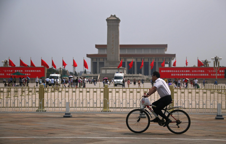 Ciclista passa em frente ao Monumento aos Heróis do Povo na Praça Tiananmen, antiga Praça da Paz Celestial, em Pequim. O governo chinês deslocou forte aparato policial nesta quarta-feira, 4 de junho de 2014, quando são celebrados os 25 anos do massacre.