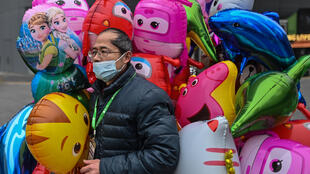 A man wearing a face mask selling balloons in Wuhan, one year after the city went into lockdown.