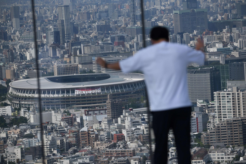 Un hombre contempla una vista de Tokio presidida por el estadio Nacional, epicentro de los próximos Juegos Olímpicos, el 21 de junio de 2021 en la capital japonesa