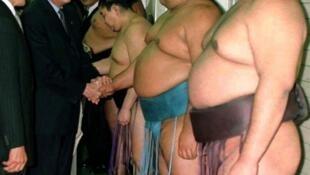 Just one of the boys: Shiraku meets a few of sumo's heavy brigade.
