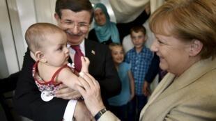 A chanceler alemã Angela Merkel e o premiê turco Ahmet Davutoglu durante uma visita a um campo de refugiados na Síria