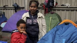 Tsega, a migrant from Eritrea with her 5-year-old son Naher in a gymnasium in Calais