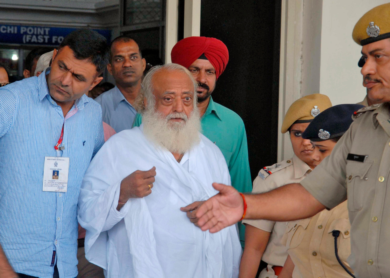 Le leader spirituel Asaram Bapu est escorté par la police en dehors d'un aéroport après son arrestation à Jodhpur, en Inde, le 1er septembre 2013