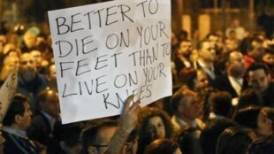 """Manifestação diante do parlamento cipriota; cartaz diz """"Melhor morrer de pé que viver de joelho""""."""