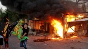 Des partisans d'une milice chiite agite des drapeaux après avoir incendié les locaux de la télévision irakienne Dijlah, accusée de diffuser de la musique lors de l'Achoura, fête religieuse chiite, à Bagdad le 31 août 2020.